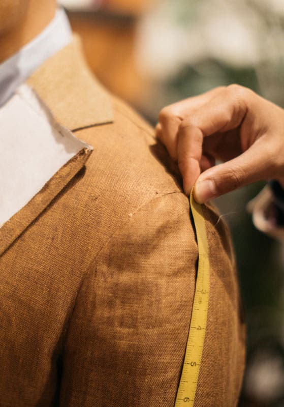 Closeup of a tailor's hand measuring the shoulder of a customer wearing an unfinished jacket prototype.