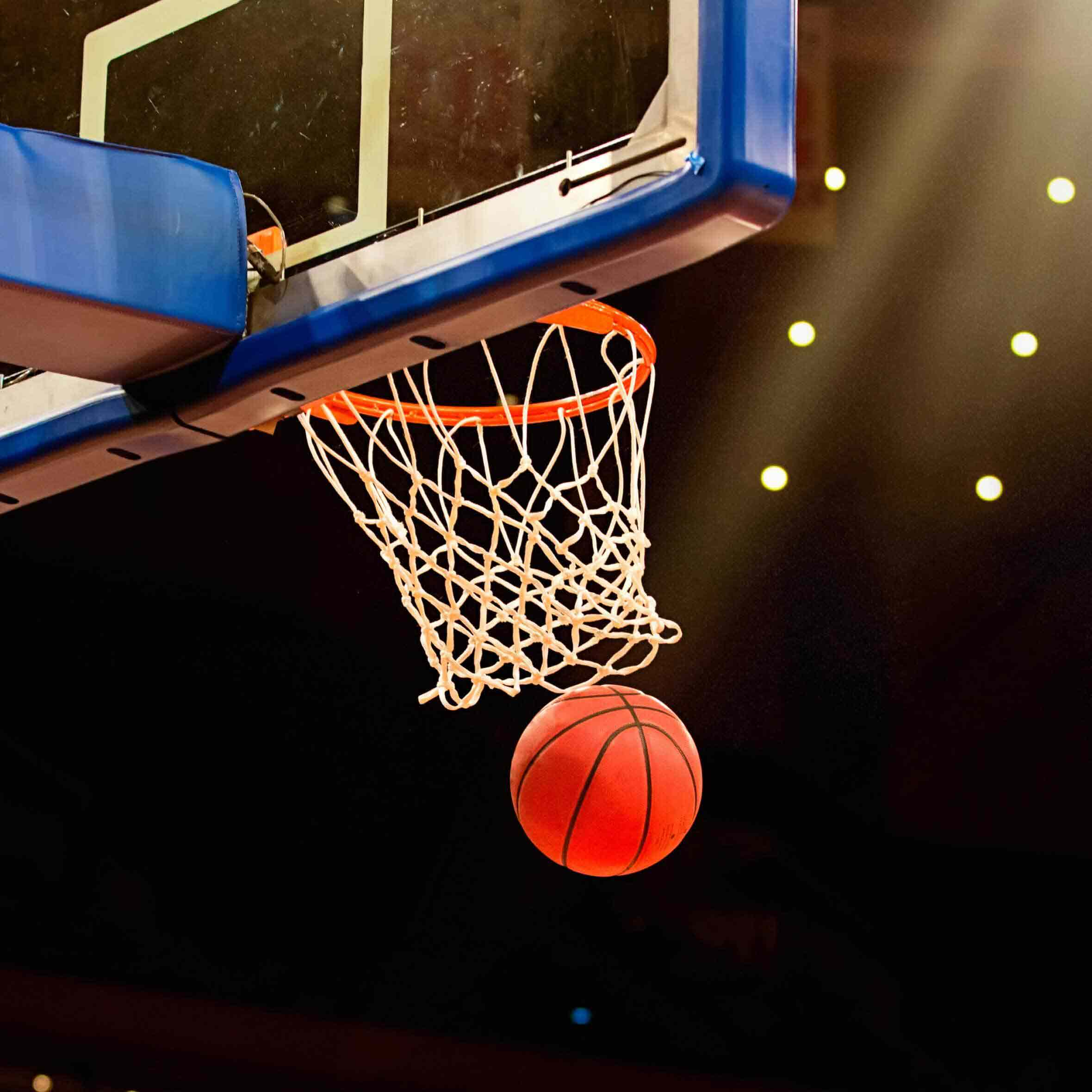 A basketball travels through a hoop during a game between professional NBA teams like the Phoenix Suns