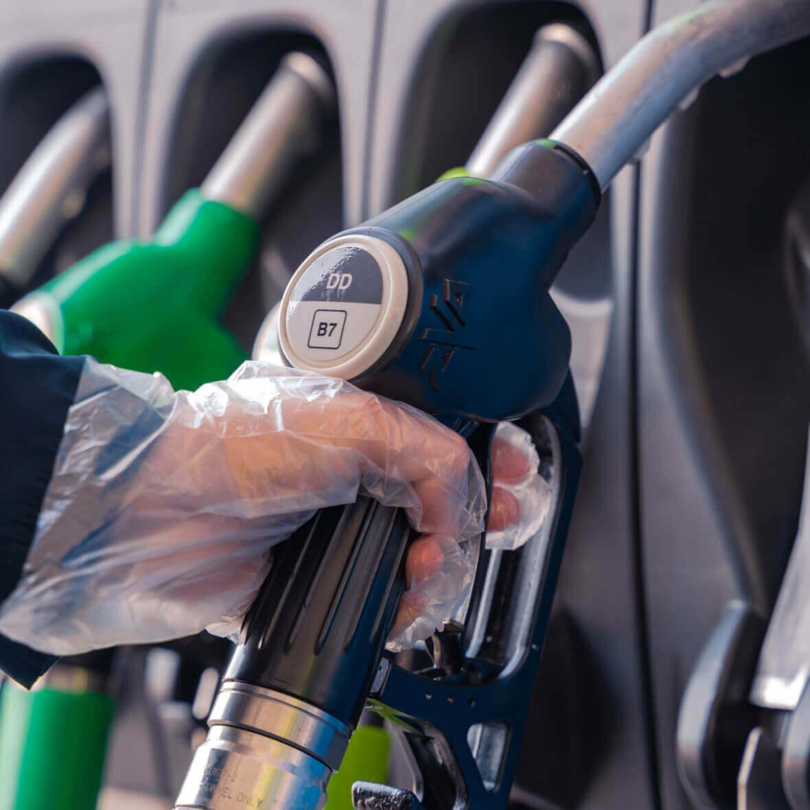 Eine Person hält den Griff einer Zapfpistole an einer Tankstelle