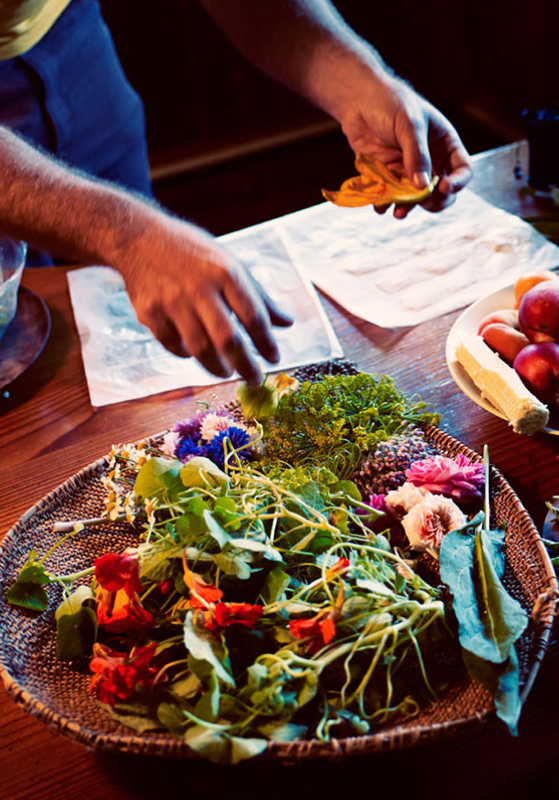 Closeup of hands arranging vegetables on table with menus.