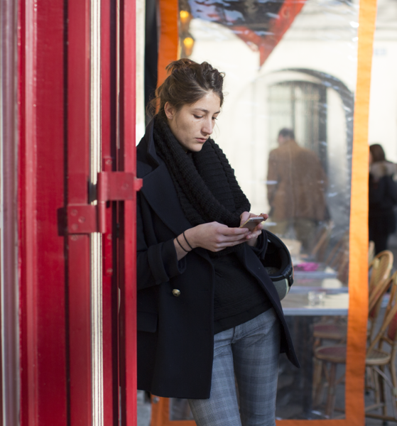 Businesswoman leaning against an exterior wall looking at her smartphone.