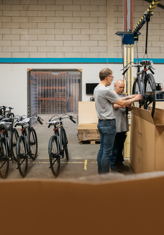 Two factory workers lowering new bicycle into shipping box.