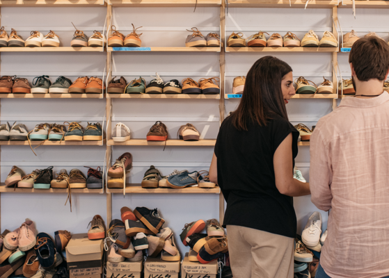 Two employees in conversation standing at a wall of shoes.