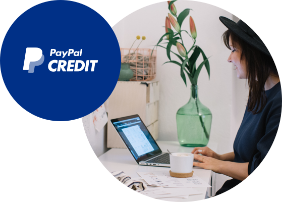 Store owner at laptop with PayPal Credit logo stacked on top.