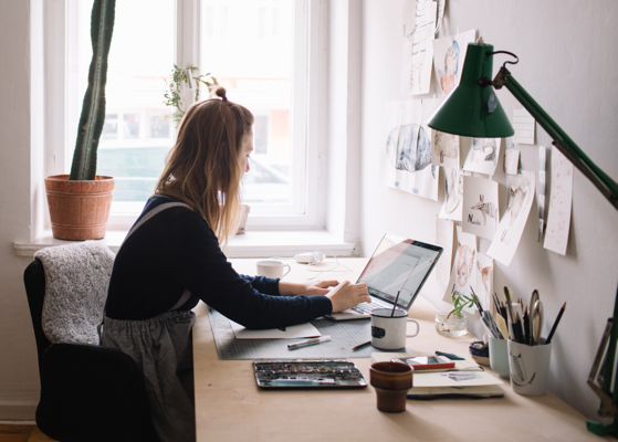 Zijaanzicht van een vrouw achter een laptop met een bureaulamp en cactus.