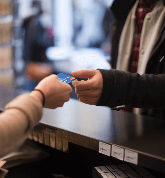The hands of a merchant and a customer swapping a credit card over a shop's counter.