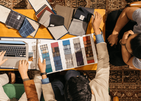 A group of tailors discussing a table full of fabric swatches.