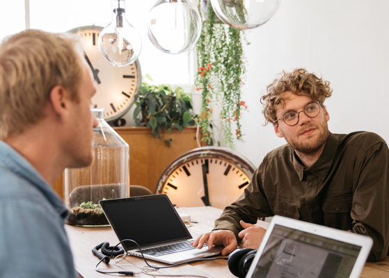 Two men in discussion, seated across a table with clocks and plants in background.