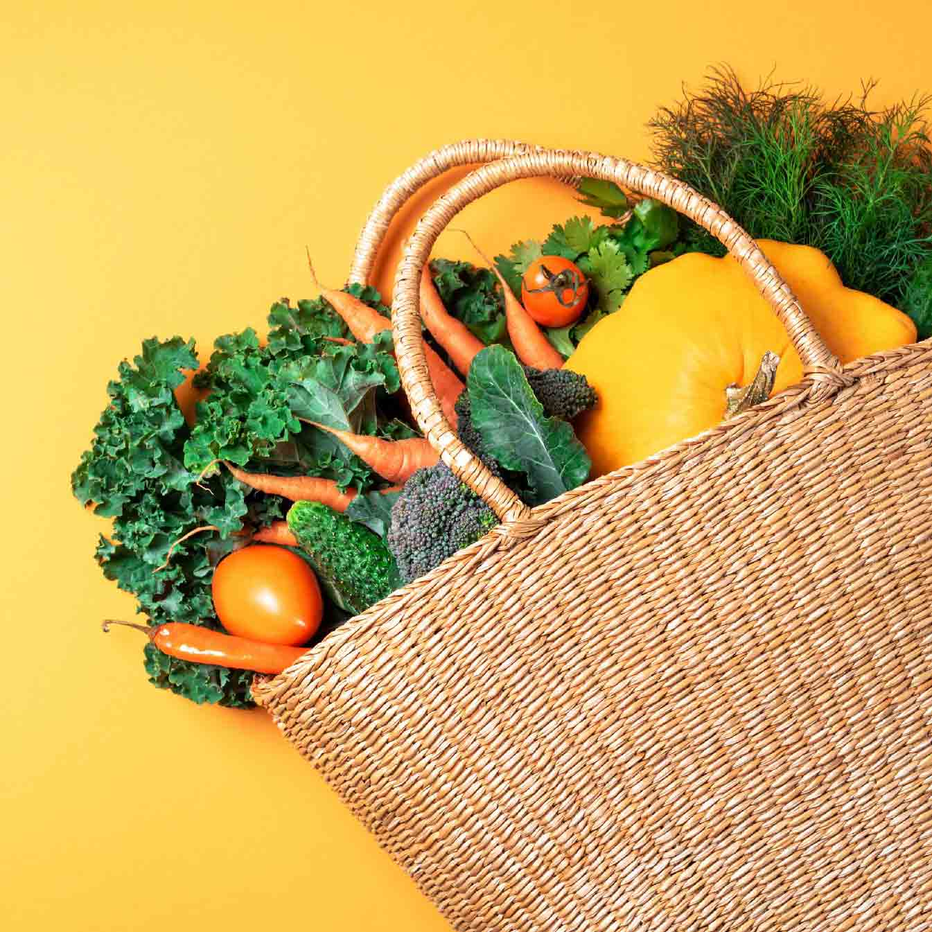 Woven shopping basket filled with vegetables similar to what is provided by Sun Basket