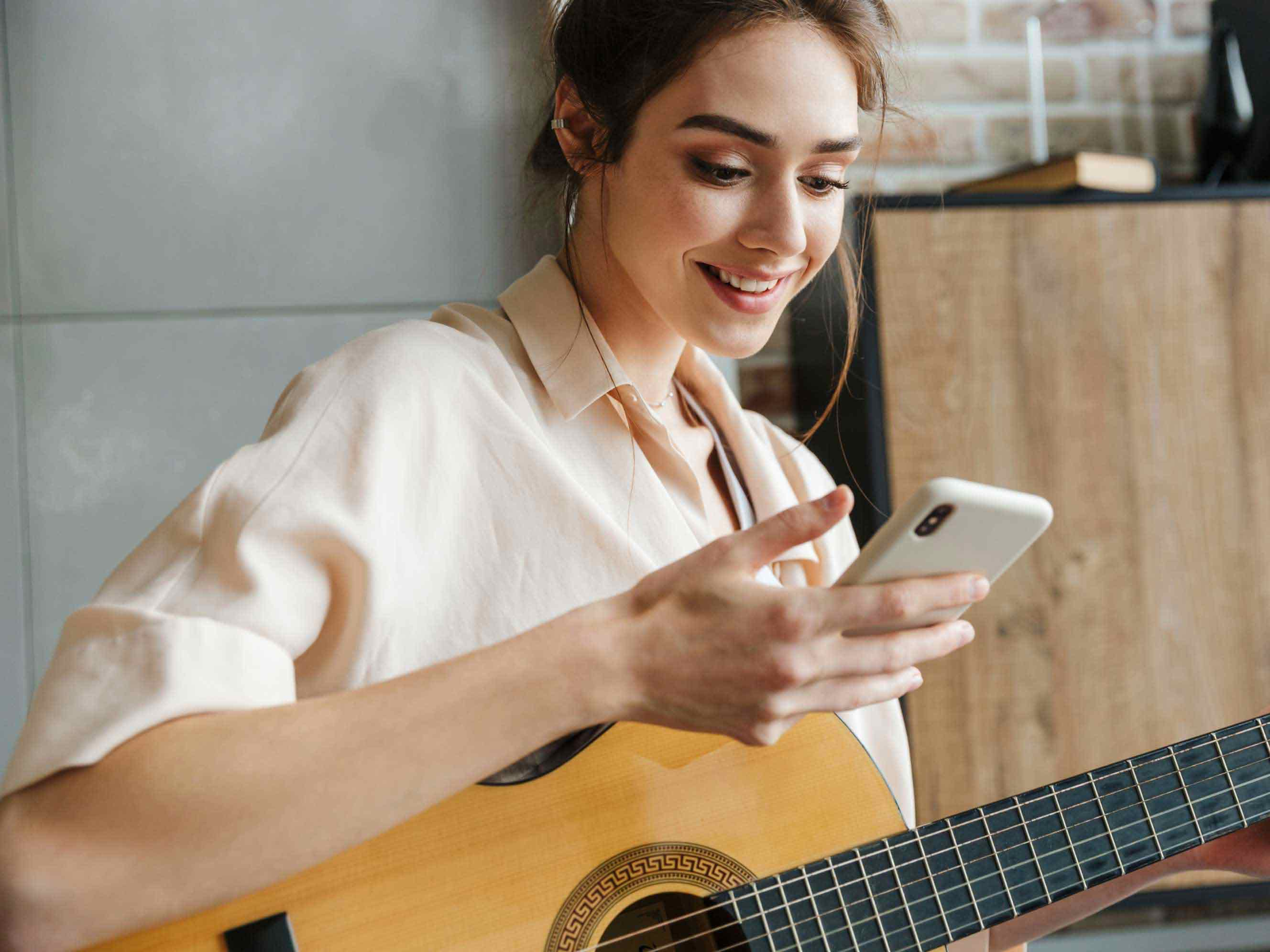Musician pauses playing her guitar to look at the notification on her phone that she's receiving money in her PayPal account