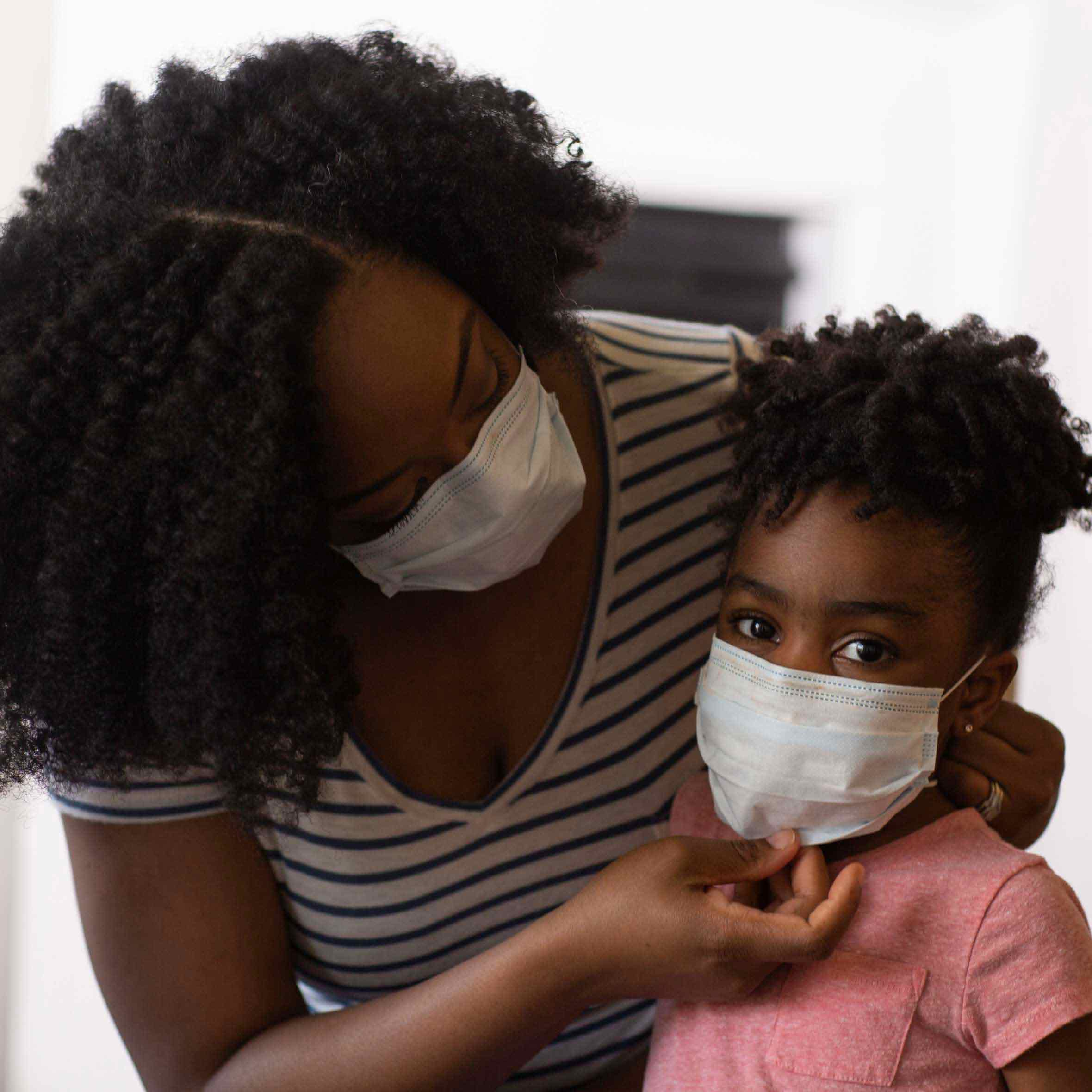 A mother and her child, who are similar to the people that GiveDirectly aids, wear face masks due to the COVID-19 pandemic