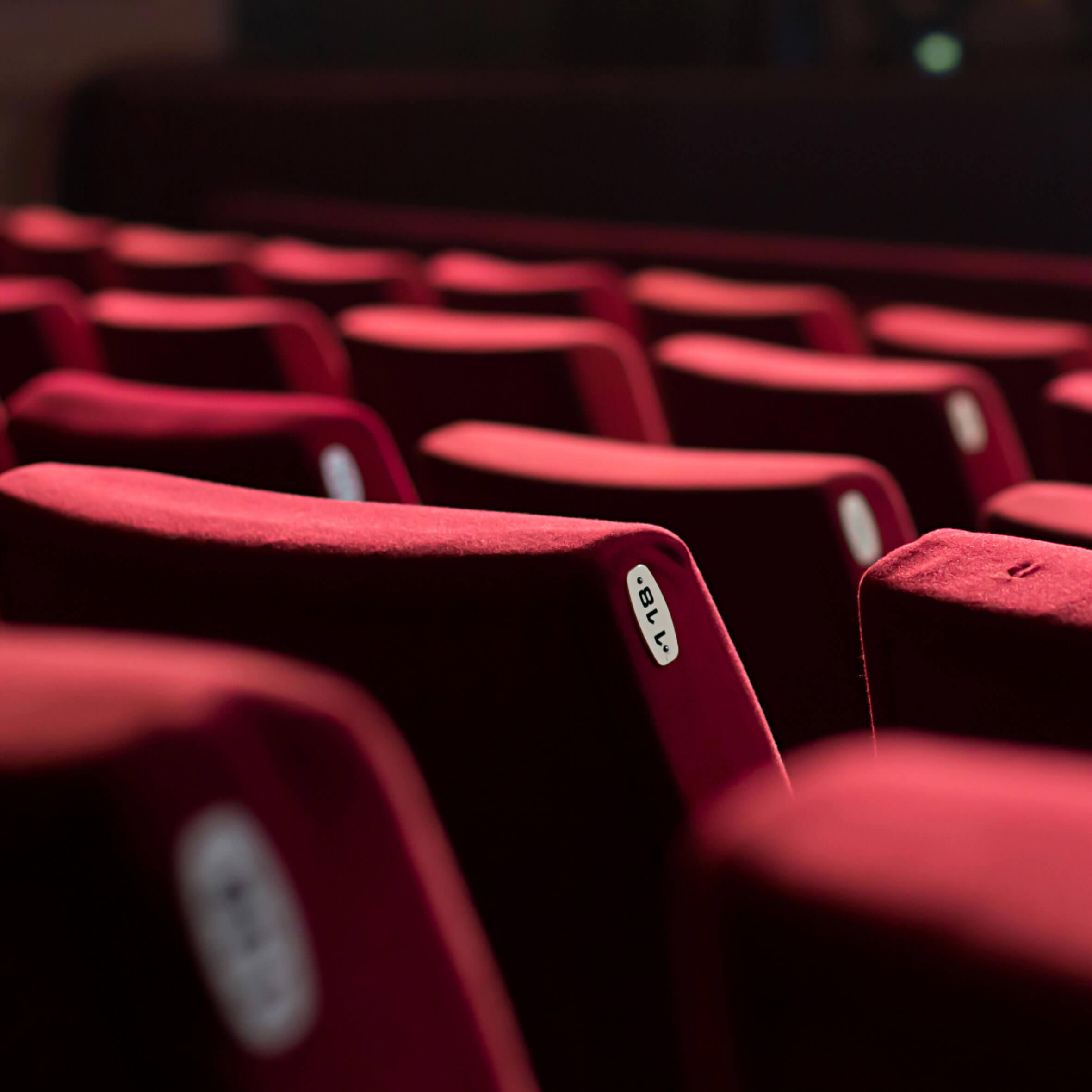 Rows of red seats in a dark theater are similar to those in the movie theaters that sell their tickets on Fandango