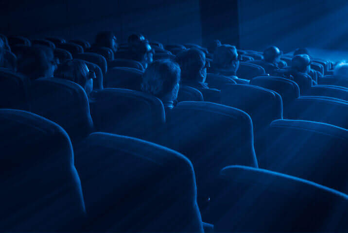 Rows of blue seats in a dark theater are similar to those in the movie theaters that sell their tickets on Fandango